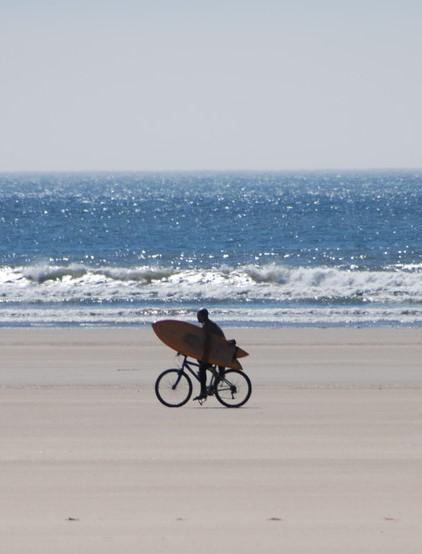 Man on bike with surfboard